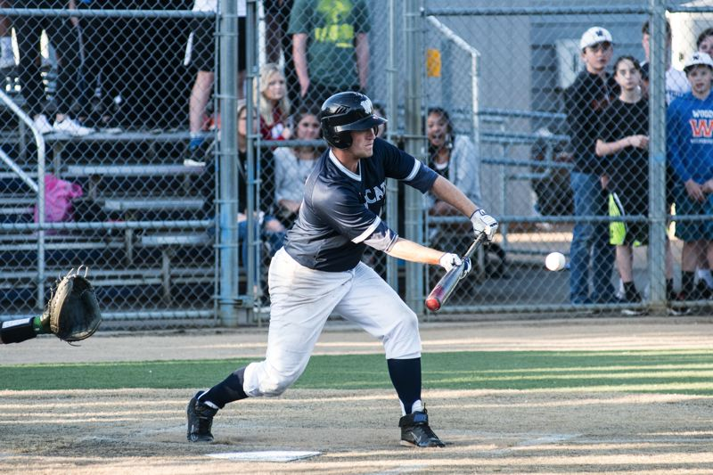 SUBMITTED PHOTO: GREG ARTMAN - Wilsonville senior Camden Crystal lays down a bunt in the bottom of the ninth inning to score Dominic Enbody and clinch the victory.
