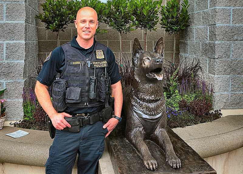 DAVID F. ASHTON - PPB Canine Unit Officer Jeff Dorn pauses for a moment next to the Canine Memorial - a sculpture of his fallen partner, Mick, whose heroic response, he says, saved his life.