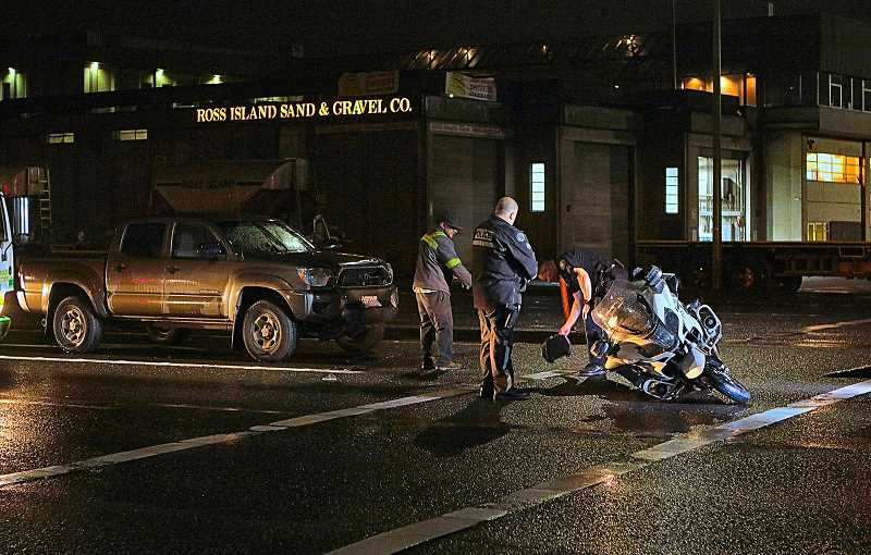 DAVID F. ASHTON - Traffic Division officers investigate a crash in which one of their own was hit from behind while stopped in a left turn lane on S.E. McLoughlin Boulevard in the Brooklyn neighborhood.