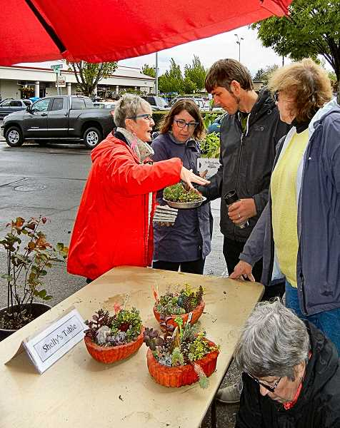 ELIZABETH USSHER GROFF - Shelly Keach, at left, explains how to make the hypertufa pots that she fills with sedums.  In April, Woodstock volunteers pitched in to make these artificial stone garden pots, which last for many years.