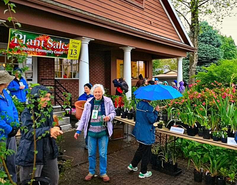 BECKY LUENING - Despite the rain on the morning of May 13, crowds of people flocked to the annual Woodstock Plant Sale at the Community Center opposite the Bi-Mart store. Terry Griffiths, at center, was the coordinator of the very successful fundraiser.