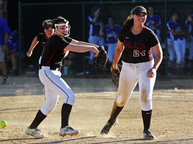 DAN BROOD - Tualatin junior Megan Woodward (left) and sophomore Emily Johansen are all smiles following the final out in the Wolves' 4-0 semifinal win over Grants Pass on Friday.