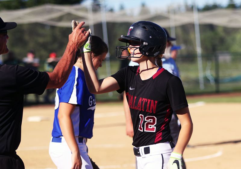 DAN BROOD - Tualatin junior Ella Hillier is congratulated by Wolves' assistant coach Bill Wilson after hitting a single in the third inning of Friday's game.