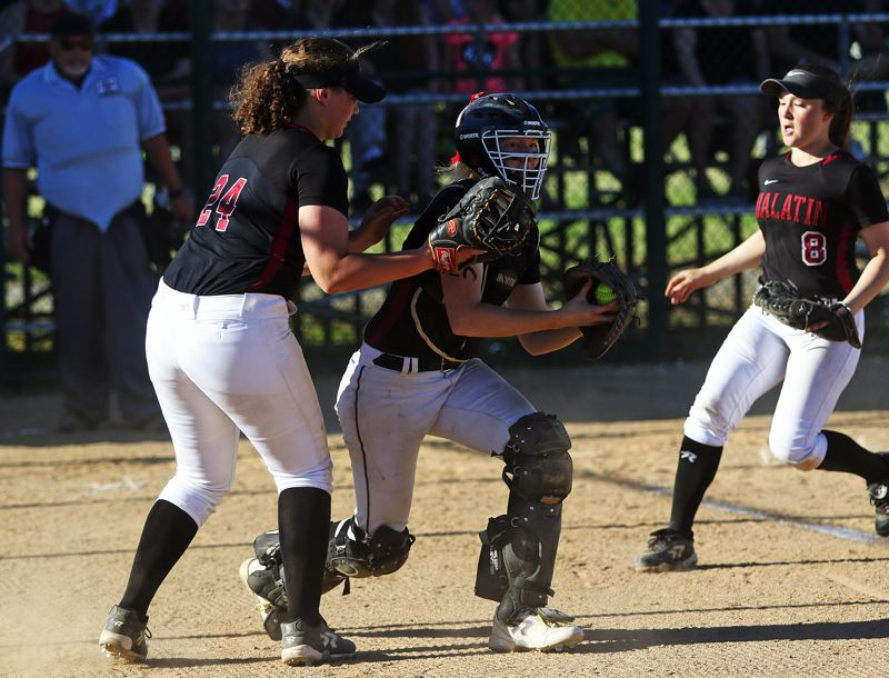 DAN BROOD - Tualatin senior catcher Sammi Caron, with sophomore first baseman Emily Johansen to her right, snags a popped-up foul ball for an out in Friday's game.