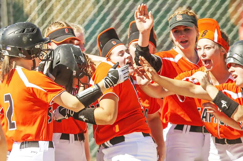 PHOTO CREDIT: JOAQUIN AGUILAR-FLORES - Senior Allyah Cates, center, and the Indians celebrate her fifth-inning home run to center in No. 9 Scappoose's 11-1 six-inning Class 4A state quarterfinal loss to top-ranked Henley on Friday, May 26, in Klamath Falls.