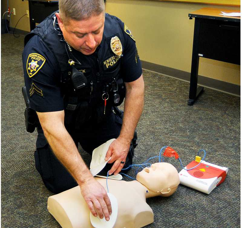 SETH GORDON - Newberg Dundee Police Corporal Del Linck runs through an AED training exercise at City Hall. Linck is one of the      department's certified  trainers in the use of the life-saving devices.