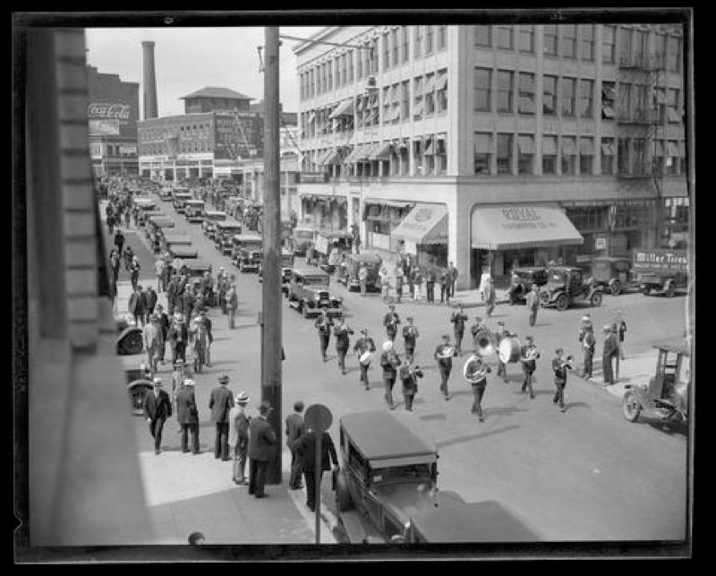 COURTESY OF THE OREGON HISTORICAL SOCIETY - A band marches down a street in 1920s downtown Portland. This photo is part of the Oregon Journal nitrate negative collection.