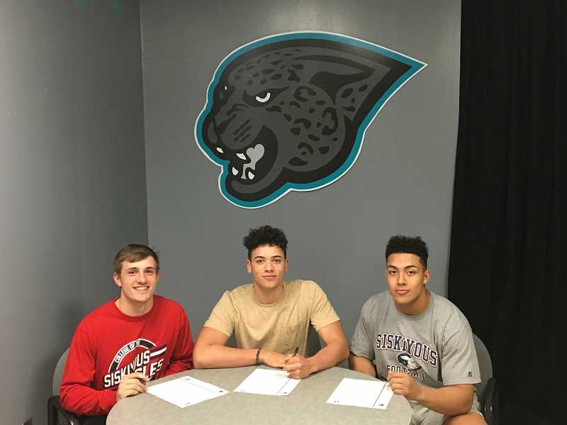 COURTESY PHOTO - Century football players Brennan Howell, Jordan Draper, and JJ Perez sign their letters of intent to play football at the College of the Siskiyous.