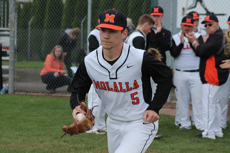 PIONEER PHOTO: CONNER WILLAMS  - Molalla senior Aaron Alexander runs out to the mound after his name is announced in the starting lineup during the Indians' senior night game against Crook County May 5.