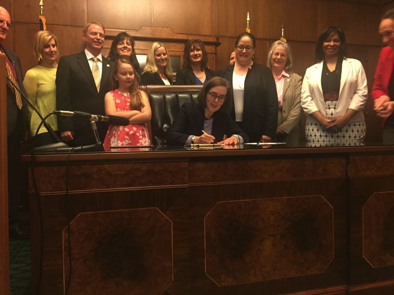 PARIS ACHEN/CAPITAL BUREAU - Gov. Kate Brown signs the 2017 Oregon Pay Equity Act into law Thursday, June 1, in her ceremonial office at the Oregon Capitol in Salem.