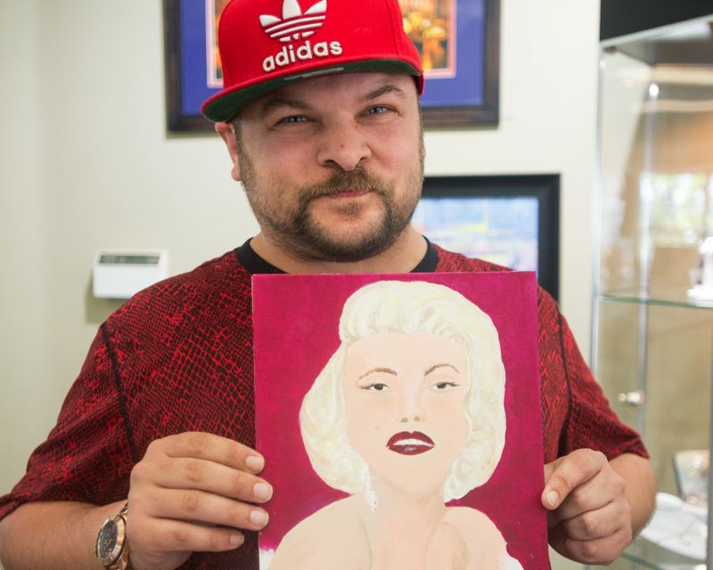 OUTLOOK PHOTO: JOSH KULLA - Artist Mike Kordowski will be the featured artist at tonight's First Friday Art Walk event in Troutdale. Here, he holds a portrait of Marilyn Monroe that he painted recently.