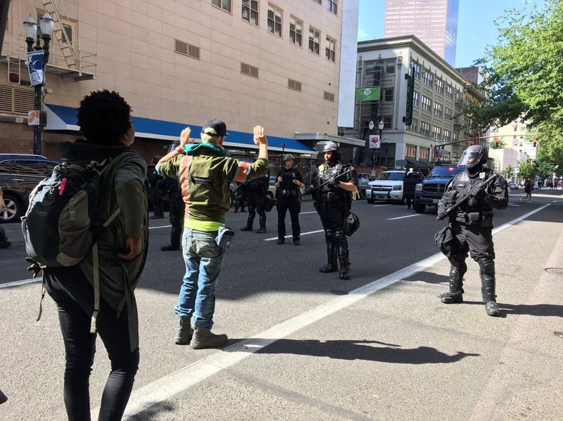 TRIBUNE PHOTO: LYNDSEY HEWITT - About a half-dozen news reporters were among the people detained by police Sunday afternoon during a rally and march through downtown streets. Hundreds of people blocked by police were under investigation for disorderly conduct.
