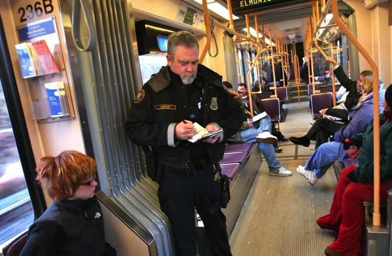 PORTLAND TRIBUNE FILE PHOTO - An armed Transit Police officer checks fares on a MAX train. TriMet is now considering whether to permanently increase security after the May 26 stabbing.