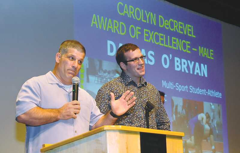 SETH GORDON - Newberg wrestling coach Neil Russo cracks a joke while presenting senior Dallas O'Bryan as the male recipient of the Carolyn DeCrevel Award of Excellence May 31 at the annual All Sports Award event.