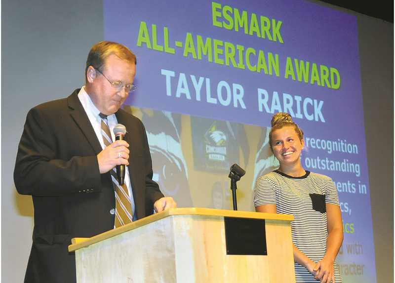 SETH GORDON - Newberg High School basketball star Taylor Rarick cracks a smile as athletic director Tim Burke presents her with the Esmark All-American Award May 31 at the annual All Sports Award event.