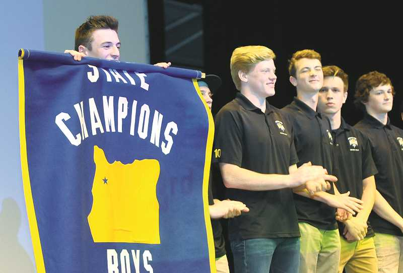 SETH GORDON - Senior Tyler Bell, left, and members of the Newberg High School water polo team unfurl their 2016 state championship banner May 31 as the annual All Sports Award event in the Drea Ferguson Auditorium.