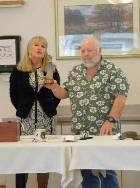 ESTACADA NEWS PHOTO: EMILY LINDSTRAND - Antique appraiser Karen Stockton discusses a musical perfume bottle brought to a show at Grace Place last week by Thomas Cherry. The bottle belonged to Cherrys great grandmother.