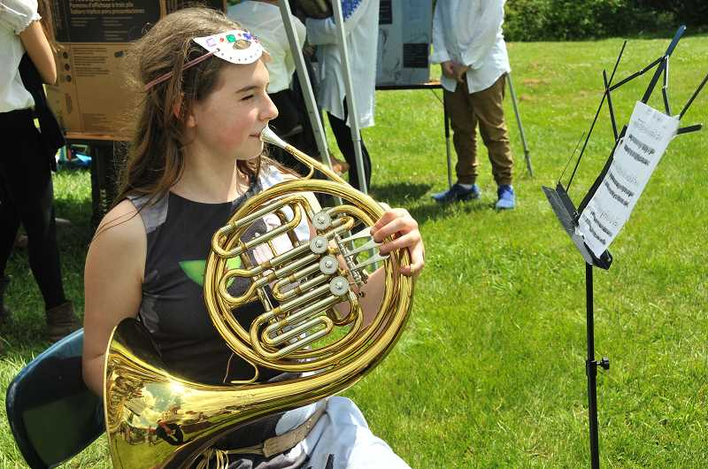 REVIEW PHOTO: VERN UYETAKE - Seventh-grader Gail Ruffer plays a Renaissance tune on the French horn during the Renaissance Faire on Friday at Lake Oswego Junior High.