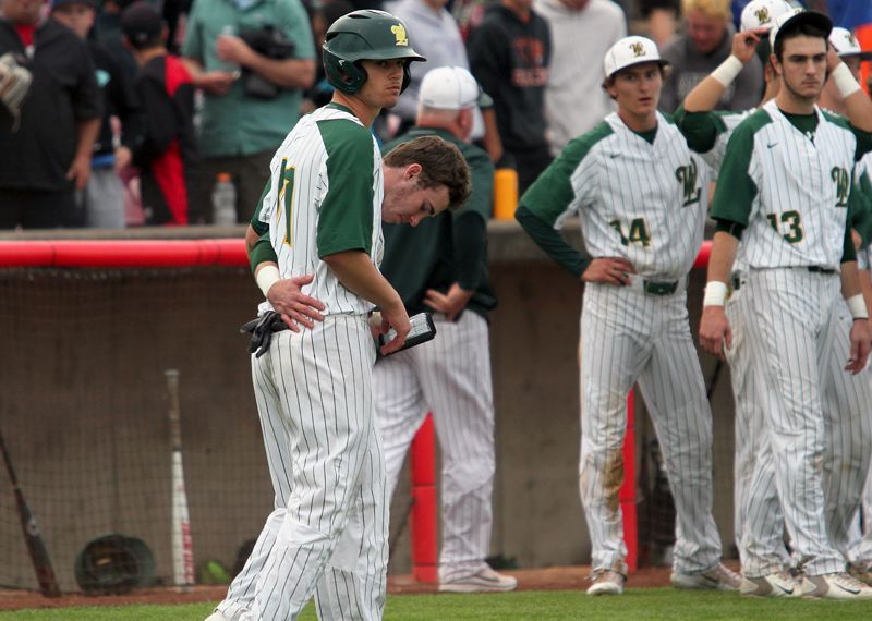 TIDINGS PHOTO: MILES VANCE - West Linn senior Tim Tawa (here with junior James Marshall) looks across the field at the celebrating Clackamas players at the end of his teams 5-1 loss to the Cavaliers in the Class 6A state championship game at Volcanoes Stadium in Keizer on Saturday.