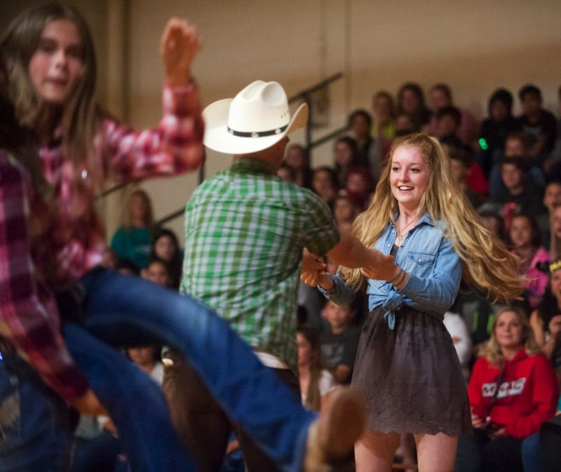 "POST PHOTO: JOSH KULLA - Social studies teacher Jeremy Wedell and eighth-grader Mayzee Dalton swing each other round and round to Big & Rich's ""Fake I.D."""