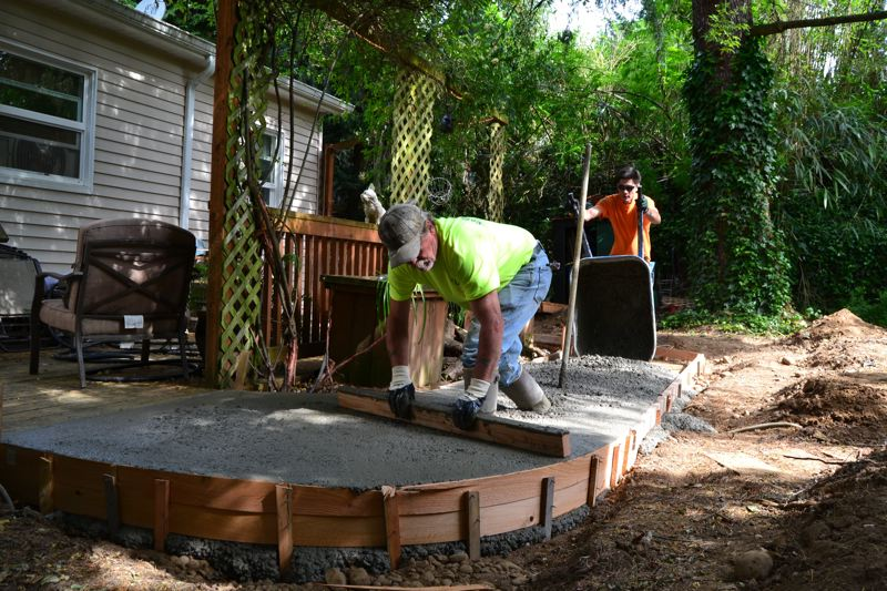 PAMPLIN MEDIA GROUP: JULES ROGERS - Dennis Brown of LaRusso Concrete is rodding with a straight edge, smoothing out the top of the ramp as the Bremik workers wheel over more.