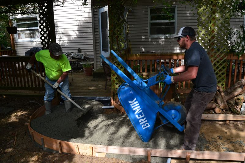 PAMPLIN MEDIA GROUP: JULES ROGERS - Brown is mucking with a mud rake, pushing the concrete into form