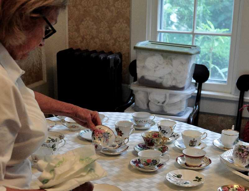 STAFF PHOTOS: LESLIE PUGMIRE HOLE - Riverview Lions Club member Susy Calhoun unpacks the myriad teacups and saucers brought out for the event each year.