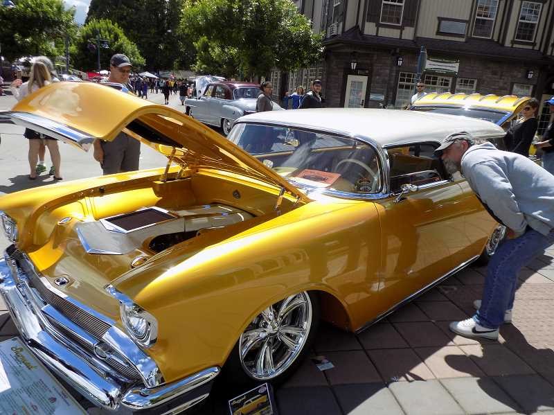GAZETTE PHOTO: RAY PITZ - A Cruisin' Sherwood attendee gets a close-up look at this yellow 1957 Chevy Nomad found sparkling in the sun on June 10.