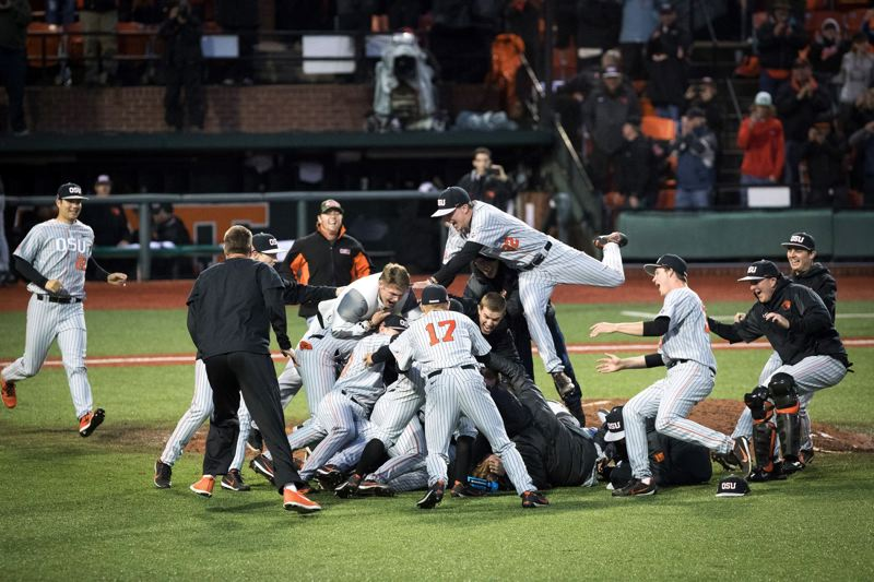 TRIBUNE PHOTO: JAIME VALDEZ - Oregon State players pile on pitcher Bryce Fehmel after his complete-game victory over Vanderbilt on Saturday night, as the Beavers earn a return trip to the College World Series.