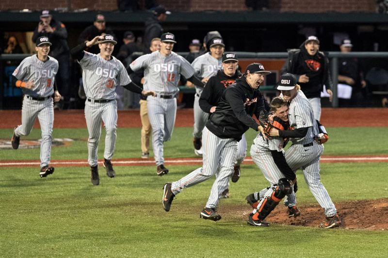TRIBUNE PHOTO: JAIME VALDEZ - Oregon State players rush onto the field to congratulate pitcher Bryce Fehmel after the Beavers'  Super Regional-clinching win Saturday night in Corvallis.