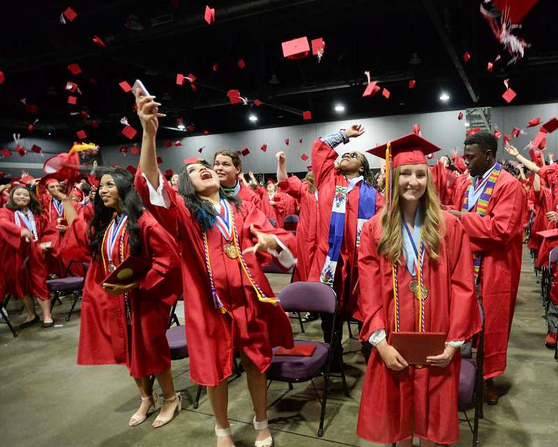 OUTLOOK PHOTO: JOSH KULLA - Class of 2017 seniors throw their caps in the air Friday night at Centennial High Schools commencement exercise at the Expo Center in North Portland.