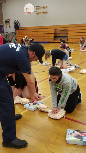 COURTESY PHOTO:  LESLIE ROBINETTE - Gladstone firefighter Izaak Thoman shows Kraxberger student Mary Grace Mott proper hand placement for CPR.