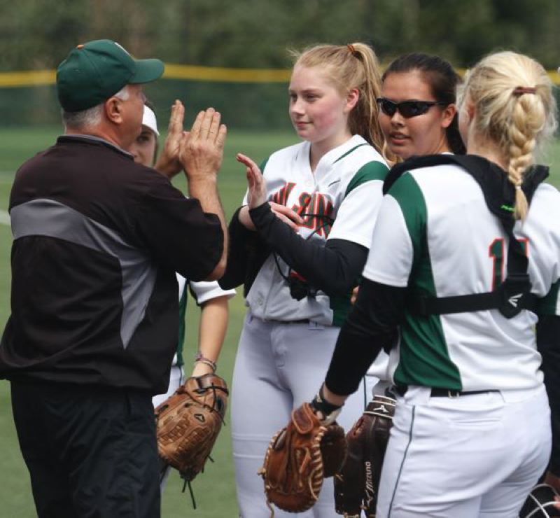 TRIBUNE PHOTO: JONATHAN HOUSE  - Wilson High softball coach Steve Walmer confers between innings of a 2017 game with Trojans (from left) Kaija Shreeve, Saioa Lostra and Ava Hergenhan.