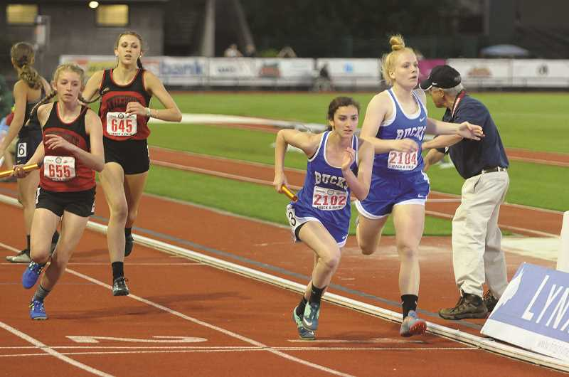SETH GORDON - St. Paul's Isabelle Wyss (far right) hands the baton off to Rachel Vela in the final leg of the 2A 4x400 relay state championship.