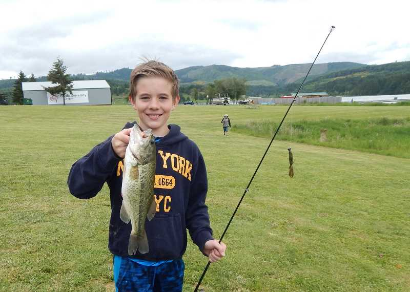 BARBARA SHERMAN - Among the Northwest Steelheaders and LRMS students fishing at Hagg Lake on May 24, five fish were caught, and Henry holds a bass he landed, which was one of two along with three trout.