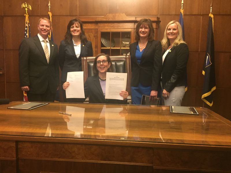 PARIS ACHEN/CAPITAL BUREAU - Gov. Kate Brown, center, holds up an equal pay bill she signed June 1, 2017, in her ceremonial office at the Oregon Capitol in Salem. Left to right, flanking her, are Sen. Tim Knopp, Sen. Kathleen Taylor, Rep. Ann Lininger, and Rep. Jodi Hack.
