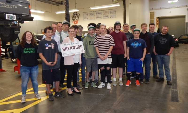 BARBARA SHERMAN - Posing with the SHS autmotive class graduates at World of Speed are (third and fourth from left) Assistant Superintendent Gary Bennett and SHS Principal Ken Bell, along with Teresa Swake, SHS advance program coordinator, holding a SHERWOOD license plate gift.