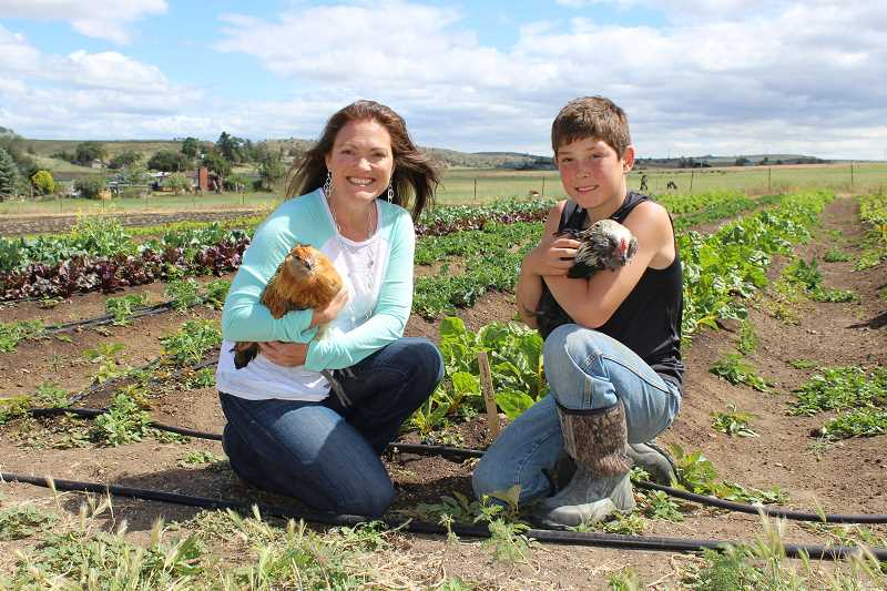 HOLLY GILL/MADRAS PIONEER - Christina Carpenter and her son, Evan, 11, hold two of the free-range chickens on the organic farm Carpenter owns with her partner, Grant Putnam. They are offering 500 RV and camping sites on the 103-acre farm near Madras.