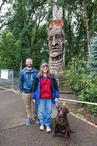 HILLSBORO TRIBUNE PHOTO: CHRISTOPHER OERTELL - Matt Maines stands with his mother Sandy and her dog Scout in front of the Chief Kno-Tah statue at Shute Park in Hillsboro. The statue was one of the first things the family saw when they moved to Hillsboro nearly 30 years ago.
