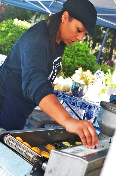 HILLSBORO TRIBUNE PHOTO: JOHN WILLIAM HOWARD - Adriane Love checks frying doughnuts at her stall along East Main Street. Mamas Minis, a Portland food card specializing in doughnuts, offered freshly-fried doughnuts with various toppings.