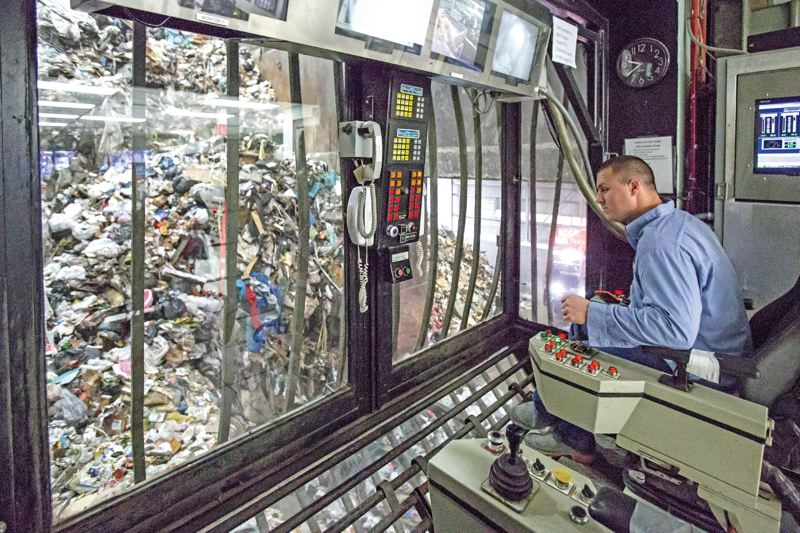 TRIBUNE PHOTO: JONATHAN HOUSE - Shane Johnson uses remote controls to maneuver an orangepeel grapple to move garbage in the refuse storage pit in Brooks. Similar to an amusement park device that lifts toys from a pile, the grapple can lift five tons of garbage in one movement.