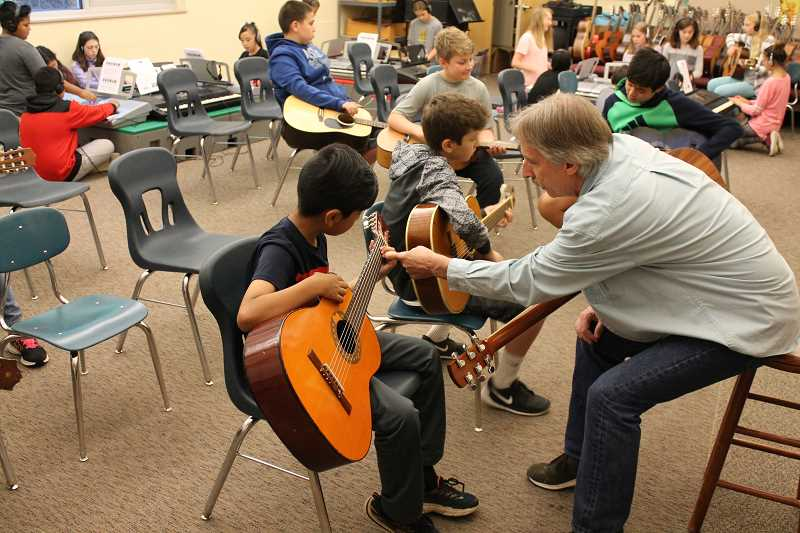 SPOKESMAN PHOTOS: ANDREW KILSTROM - Musician John Nilsen helps with finger placement during music class at Boones Ferry Primary on Thursday, June 9.