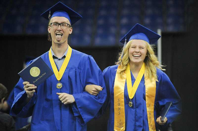 OUTLOOK PHOTO: JOSH KULLA - Barlow graduates Zander Standish and Kyla Penrod laugh as they march down the Memorial Coliseum ramp Tuesday after receiving their diplomas.