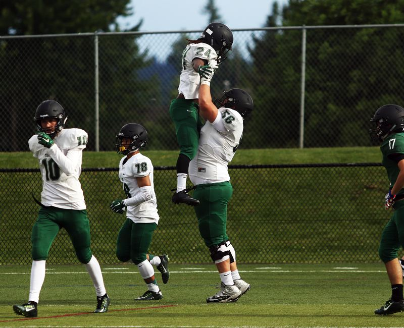DAN BROOD - White team running back Malcome Stockdale is lifted high into the air by Burke Albaugh after scoring on a 70-yard run in the Tigard Chicken and Bean Bowl.