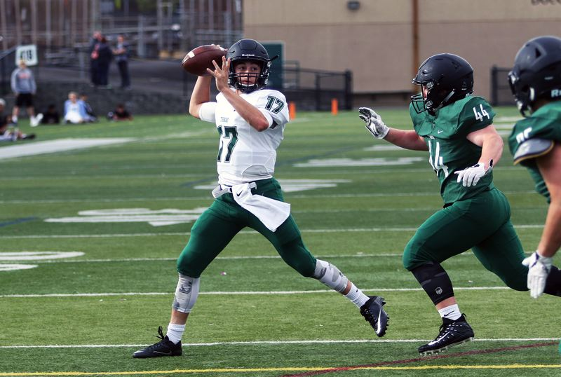 DAN BROOD - White team quarterback Michael Quintana rolls out to pass during Saturday's Tigard Chicken and Bean Bowl.