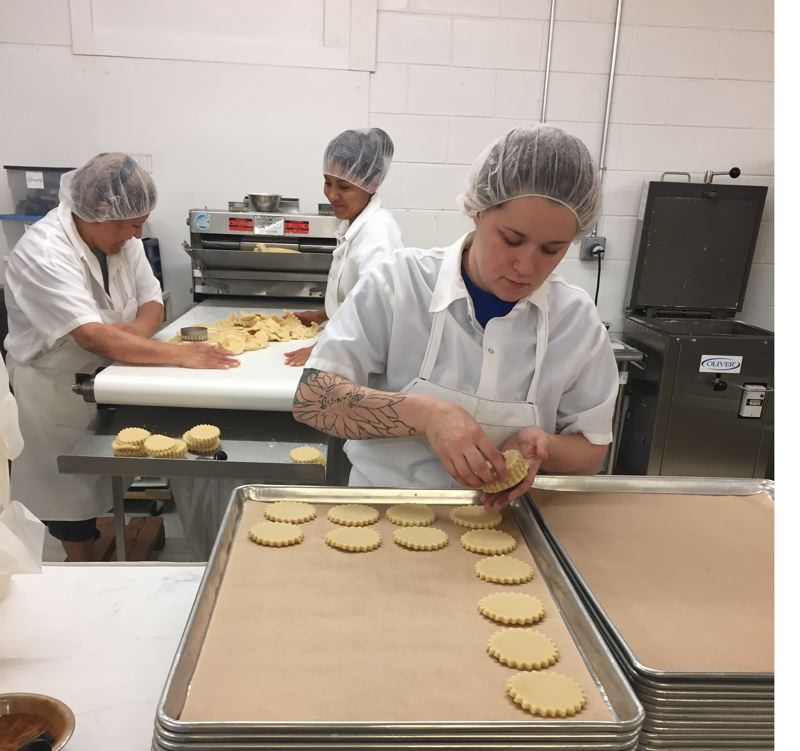 COURTESY: OMEP - A worker at McTavish Cookie Company near Gateway lays out shortbread for a baking. New food safety rules will take the company a lot of time and money to follow, according to owner Denise Pratt, but she believes they are good for the industry in the long run. (Above and below) Workers at food processing plants will have to clean more, and document their cleaning.