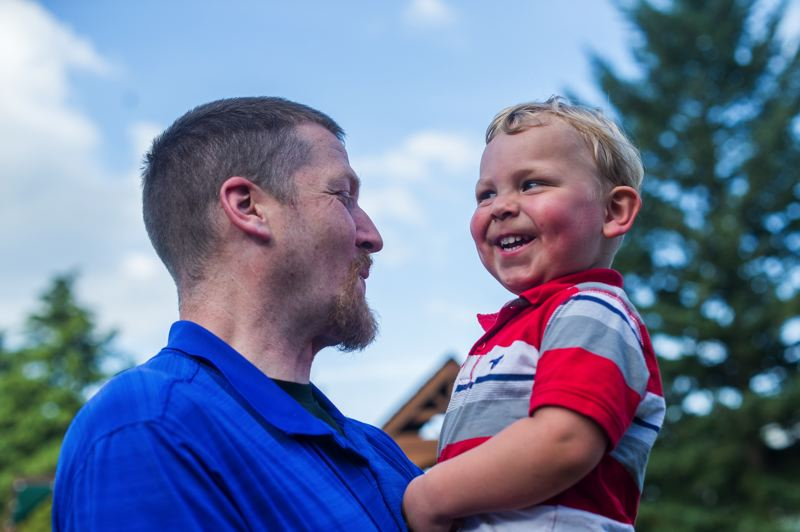 OUTLOOK PHOTO: JOSH KULLA - Dan Hermann gets a huge grin from his 2-year-old foster child E. Hermann and his wife, Summer, are in the process of adopting E and his sister.