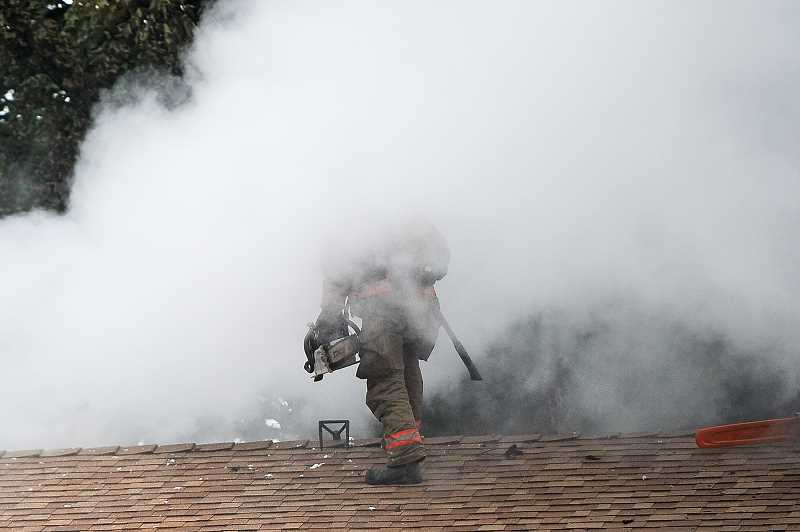 OUTLOOK PHOTO: JOSH KULLA - A Gresham firefighter cuts a hole in the roof of an apartment at the Rosewood Commons in Gresham after a fire broke out this afternoon, leaving a man dead and a woman suffering from smoke inhalation.