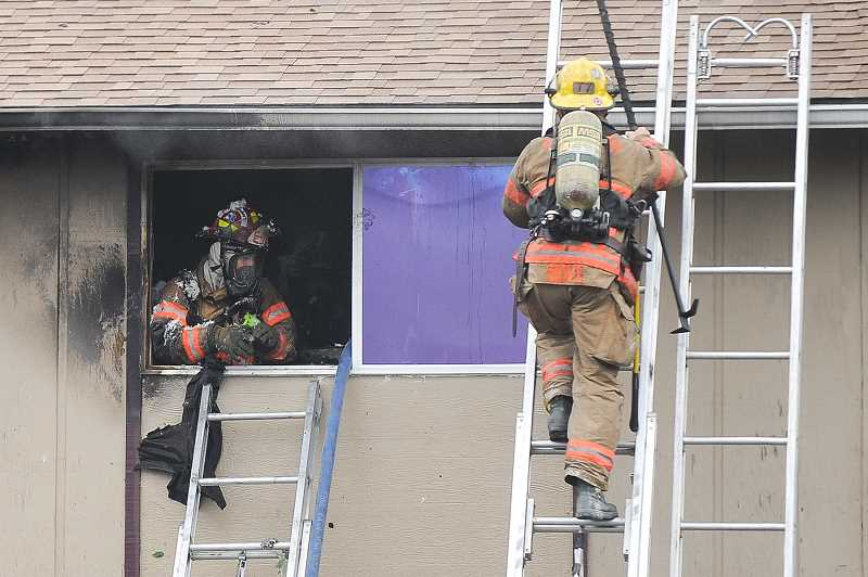 OUTLOOK PHOTO: JOSH KULLA - Gresham firefighters work on the remnants of a fire at the Rosewood Commons apartment complex this afternoon. One man was killed in the second-story blaze.