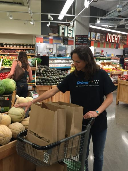 PAMPLIN MEDIA GROUP - An Amazon Prime Now employee shops at New Seasons Market for two hour home delivery in Portland.  The hard-driving retailer teamed with eco grocers and cup cake shops for two hour delivery in select zip codes; now it is going the whole hog and buying 400 plus Whole Foods stores.
